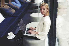 Lovely student with a beautiful smile and short hair and a white pullover sitting in a trendy bar with laptop computer Royalty Free Stock Photography