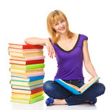 Lovely student sitting on a floor with stack of books, isolated Royalty Free Stock Photography