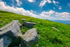 Lovely summer landscape. Grassy hillside with rocky formations. cloud behind the mountain peak in the distance. bright and fresh day, good mood. wonderful royalty free stock images