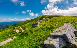 Lovely summer landscape. Grassy hillside with rocky formations. cloud behind the mountain top. bright and fresh day, good mood. wonderful place for hiking and stock image