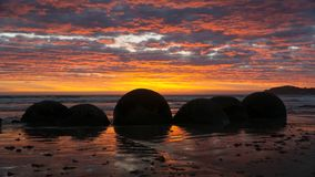 Lovely sunrise in front of mysthical Moeraki boulders, New Zealand stock photography