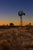 Lovely sunset in Kalahari with windmill and grass Royalty Free Stock Photo