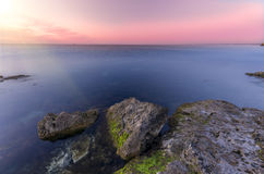 Lovely sunset. Overlooking the sharp rocky shore of the ocean stock image