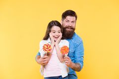 Lovely surprise. Girl cheerful child and dad hold colorful lollipops. Sweet dessert concept. Bearded hipster good daddy. For adorable daughter. Daughter and royalty free stock photos