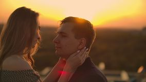Lovely sweet happines couple sit on the roof top with amazing sunset view on the urban city town. They love each other