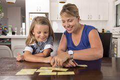 Lovely sweet and happy 6 years old daughter learning reading with flash card words game at home kitchen playing with her young bea Stock Image