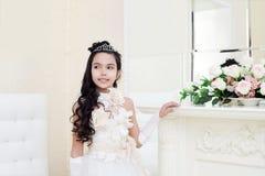 Lovely tanned girl posing in elegant white dress Royalty Free Stock Photography