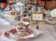 Lovely tea time table setting. Tea time in Placitas, New Mexico. Elegant and beautiful tea time place settings surrounded by  dainty white and peach roses Royalty Free Stock Photo