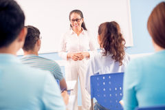 Lovely teacher. Image of a middle-aged teacher standing in front of the class on the foreground Stock Images