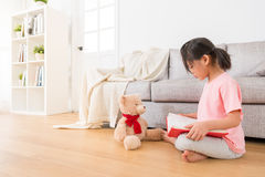 Lovely teddy bear accompanied with. Kindergarten little girl reading book at home in the living room and children learn to read English books in the morning of royalty free stock images