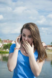 Lovely teen girl with enthusiasm talking on the phone and receiving surprise. Royalty Free Stock Photography