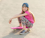 Girl with long hair sitting on skating board Royalty Free Stock Photo