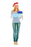 Lovely teen girl in Santa hat presenting gift Stock Photo