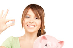 Lovely teenage girl with piggy bank and coin Stock Photography