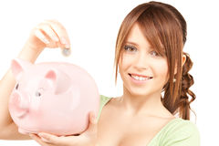 Lovely teenage girl with piggy bank and coin Royalty Free Stock Photos