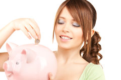 Lovely teenage girl with piggy bank and coin Stock Photos