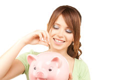 Lovely teenage girl with piggy bank and coin Royalty Free Stock Photo