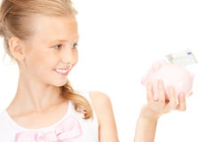 Lovely teenage girl with piggy bank and money Stock Photo
