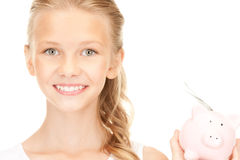 Lovely teenage girl with piggy bank and money Stock Image