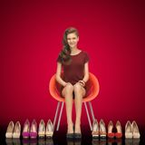 Lovely teenage girl in red dress with shoes Stock Image