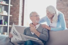So lovely and tender old couple! A grandfather is reading a news. Paper and telling the latest news to his lovable wife who is hugging him Royalty Free Stock Image