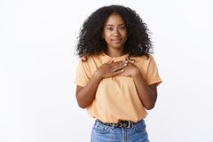 Lovely thankful attractive young african-american girl curly haircut press palms chest grateful appreciation gesture. Smiling thanking effort receive royalty free stock photography