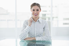 Lovely thinking businesswoman sitting at her desk smiling at camera Stock Images