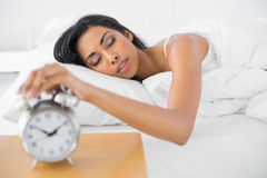 Lovely tired woman turning off the classic alarm clock. Lying in her bed Royalty Free Stock Images