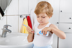 Lovely toddler with blue eyes and blond hair brushing his teeth Royalty Free Stock Images