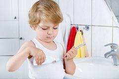 Lovely toddler boy brushing his teeth, indoors Stock Photos