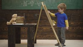 Lovely toddler boy drawing on chalkboard on wooden background. Small artist paints on a wooden background. Concept of. Fine art. Smart little fellow studying stock footage