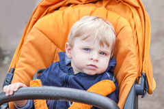 Lovely toddler boy outdoor in orange stroller Stock Photo