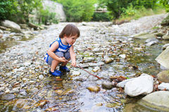 Lovely toddler boy plays with stick in flashy river Stock Images