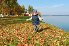 Lovely toddler boy running in autumn outdoors Royalty Free Stock Photos
