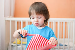 Lovely toddler boy with scissors cutting paper at home Royalty Free Stock Photography