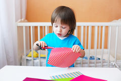Lovely toddler boy with scissors cutting paper Royalty Free Stock Images