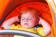 Lovely toddler boy sleeping outdoor in orange stroller. Royalty Free Stock Photo