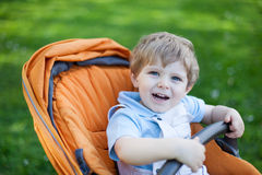 Lovely toddler boy smiling outdoor in orange stroller Stock Photography