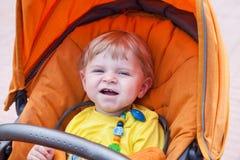 Lovely toddler boy smiling outdoor in orange stroller Royalty Free Stock Image