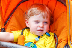 Lovely toddler boy smiling outdoor in orange stroller Royalty Free Stock Image