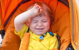 Lovely toddler boy smiling outdoor in orange stroller Royalty Free Stock Photography