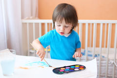 Lovely toddler with brush and paints at home Royalty Free Stock Photography