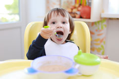 Lovely toddler eating oatmeal Stock Images
