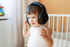 Lovely toddler listening to music with headphones Stock Photos