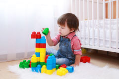 Lovely toddler playing constructor at home Stock Photos