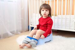 Lovely toddler sitting on potty. Little boy sitting on potty at home stock photos