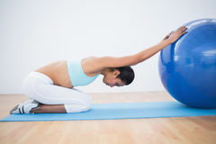 Lovely toned woman stretching her body with exercise ball Royalty Free Stock Images
