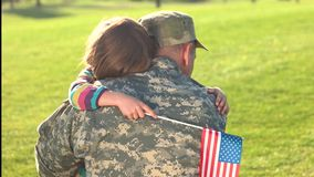 Lovely touching hugs of little girl with her military father came back. Daughter with USA background embracing her soldier daddy on park grass background stock footage