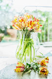 Lovely tulips bunch in glass vase with water on table at spring day background Stock Photo