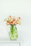 Lovely tulips bunch in glass vase on white table at white wall. Home interior concept. Royalty Free Stock Photo